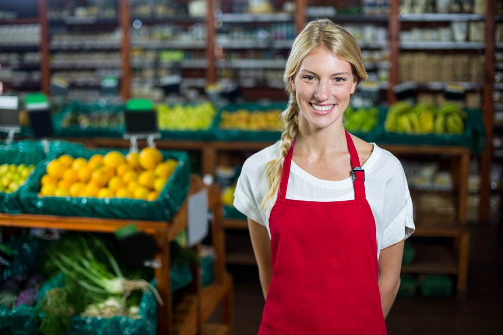 Portrait of smiling female staff standing in organic section of supermarket.jpeg