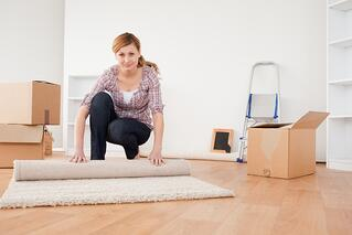 Pretty blonde woman rolling up a carpet to prepare to move house.jpeg