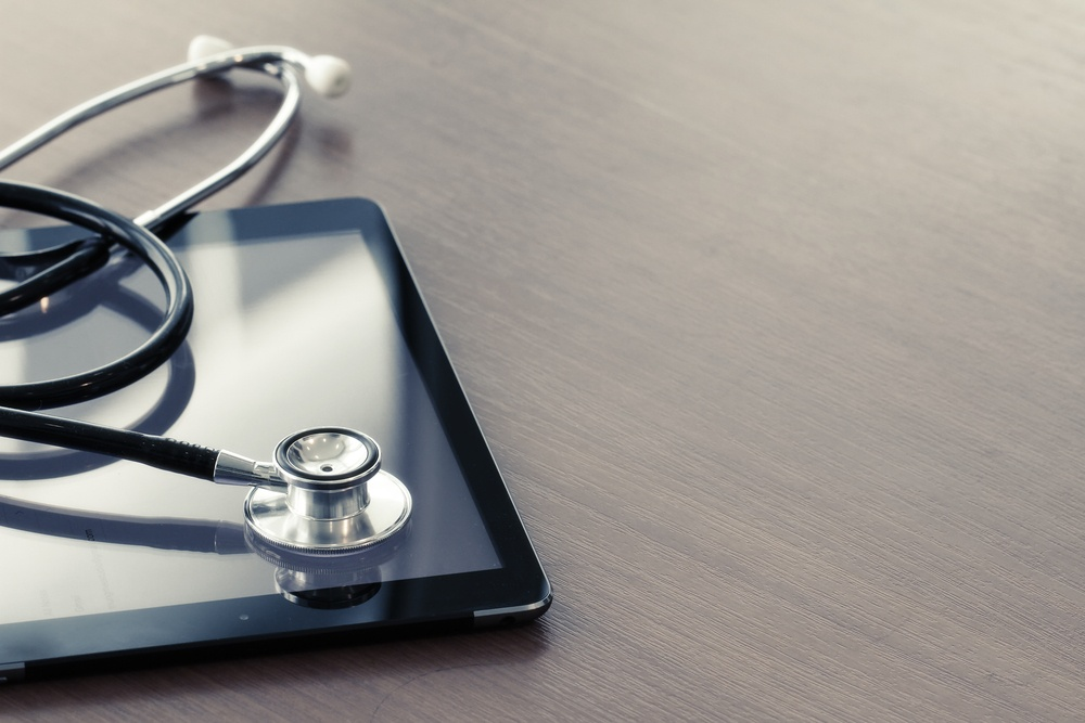 Studio macro of a stethoscope and digital tablet with shallow DOF evenly matched abstract on wood table background copy space.jpeg